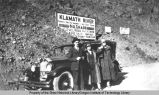 "Two women and a man in front of their car. Sign in background says ""Klamath River  Famous for..."